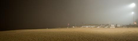 Восьмого мая в Агадире целый день светило солнце, было жарко, а к вечеру вдруг с океана побежали облака и на песчаный пляж, как будто, надвинулся туман. Он набегал на берег мутной пеленой и застилал все вокруг. К вечеру вдоль набережной зажгли огни. Я взял камеру и пошел вниз, к воде. Это был не обычный туман, конечно. В воздухе висела мелкая пыль — песок, прилетевший из Сахары, но появившийся здесь почему-то со стороны Атлантического океана. Было абсолютно тихо, безветренно. В свете сильных ламп пляж выглядел странным и загадочным.